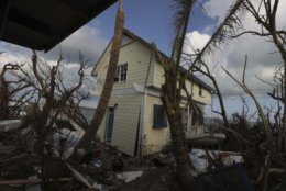 A home damaged by Hurricane Dorian is surrounded by debris in Eastern Shores just outside of Marsh Harbor, Abaco Island, Bahamas, Saturday, Sept. 7, 2019. The Bahamian health ministry said helicopters and boats are on the way to help people in affected areas, though officials warned of delays because of severe flooding and limited access. (AP Photo/Fernando Llano)