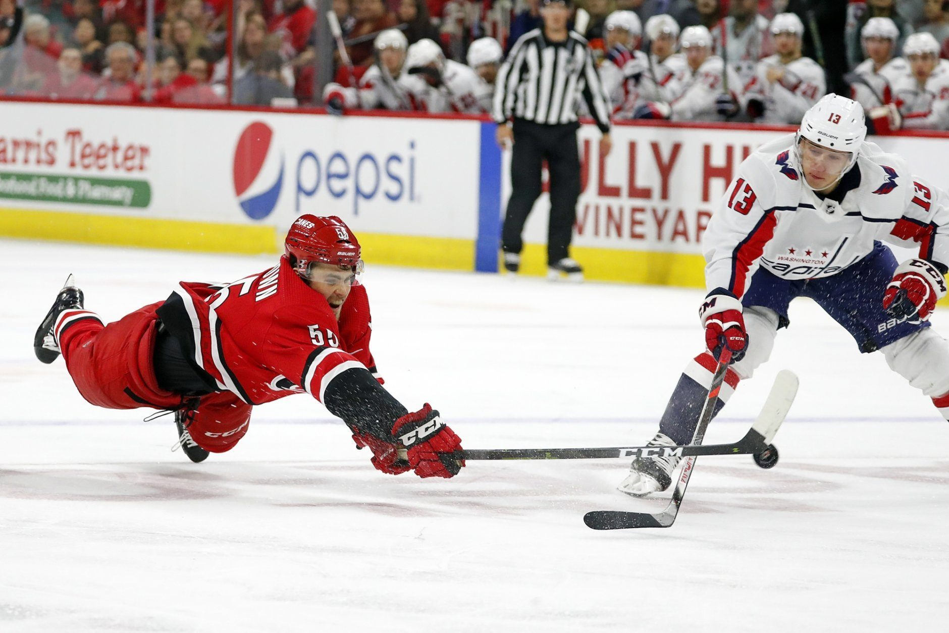 Carolina Hurricanes' Roland McKeown (55) dives to tip the puck away from Washington Capitals' Jakub Vrana (13), of the Czech Republic, during the third period of an NHL preseason hockey game in Raleigh, N.C., Sunday, Sept. 29, 2019. (AP Photo/Karl B DeBlaker)