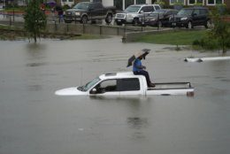 A man sits on top of a truck on a flooded road, Thursday, Sept. 19, 2019, in Houston. Members of the Houston Fire Dept. brought him a life jacket and walked him to dry land. Throughout Texas and Louisiana, the remains of Tropical Depression Imelda kept bringing rains and flooding. (Melissa Phillip/Houston Chronicle via AP)