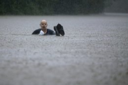 A man wades out through floodwaters caused by heavy rain spawned by Tropical Depression Imelda inundated the area on Thursday, Sept. 19, 2019, in Patton Village, Texas. (Brett Coomer/Houston Chronicle via AP)