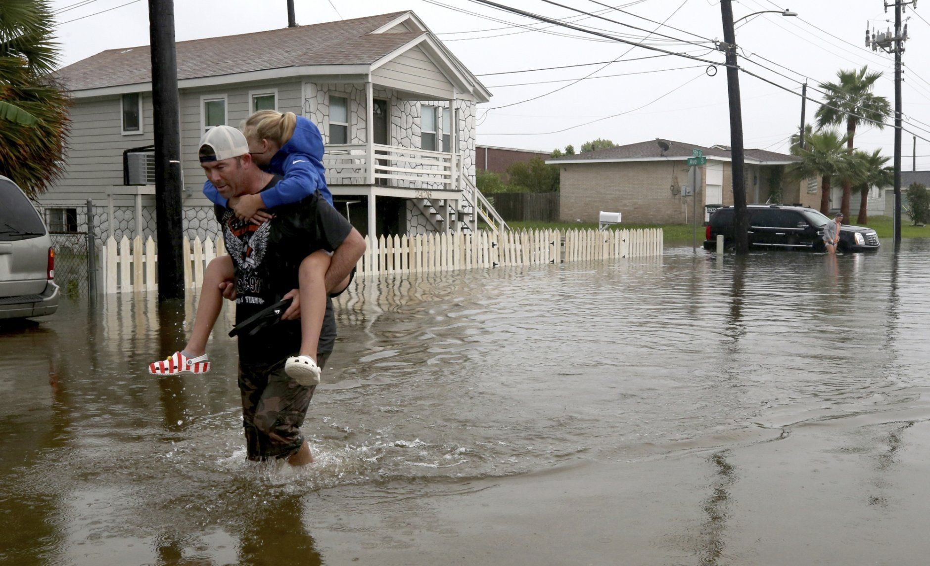 Terry Spencer carries his daughter, Trinity, through high water on 59th Street near Stewart Road in Galveston, Texas, Wednesday, Sept. 18, 2019, as heavy rain from Tropical Depression Imelda caused street flooding on the island. (Jennifer Reynolds/The Galveston County Daily News via AP)