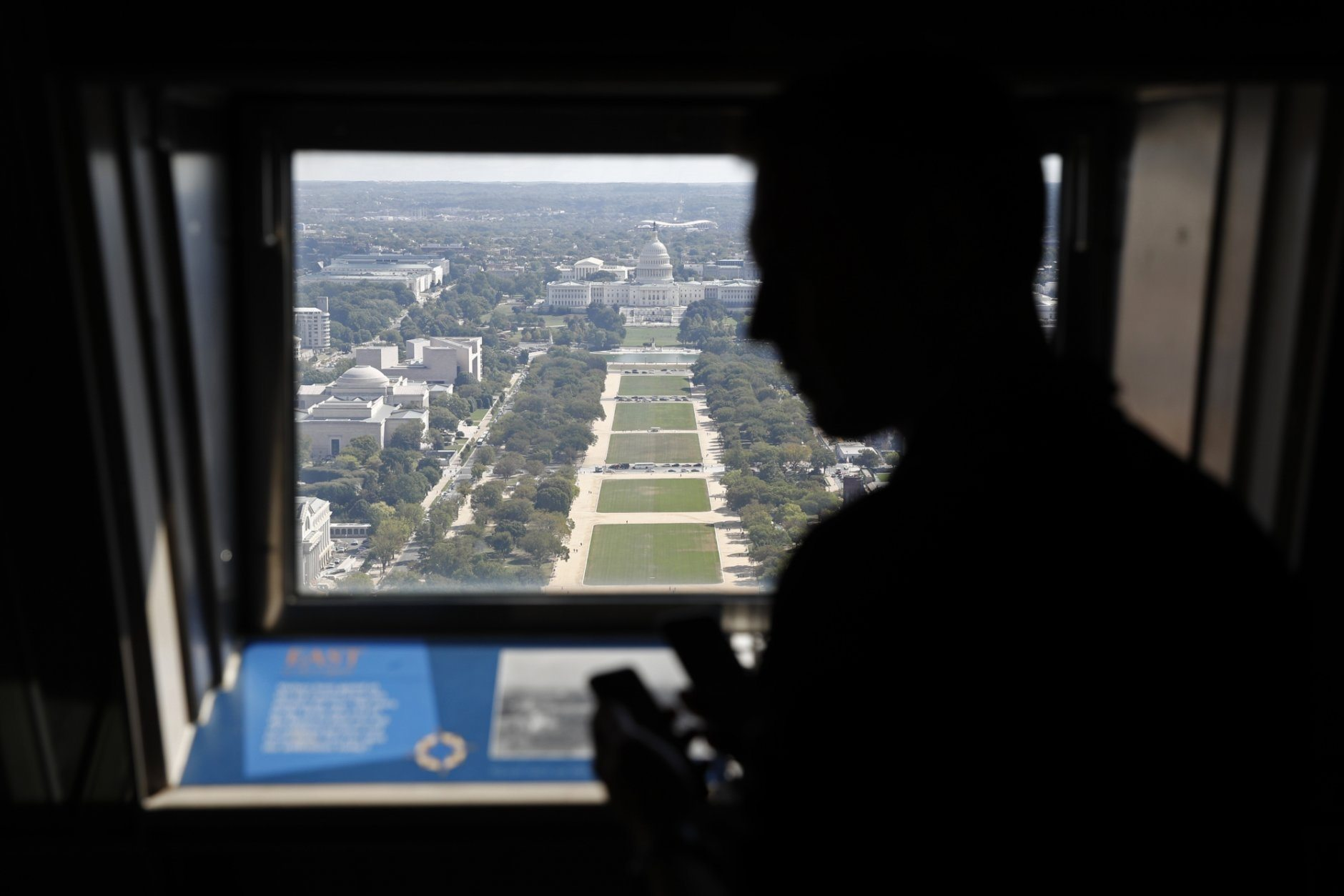 A visitor looks out toward the U.S. Capitol from the Washington Monument's observation level during a press preview tour ahead of the monument's official reopening, Wednesday, Sept. 18, 2019, in Washington. The monument, which has been closed to the public since August 2016, is scheduled to re-open Thursday, Sept. 19. (AP Photo/Patrick Semansky)