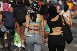 "FILE - In this March 8, 2019 file photo, women hold hands as they walk with Spanish slogans printed on their backs, reading, from left, ""My body, my rules,"" and ""We are going to tear down [the patriarchy]"" during a protest march in Mexico City. The United Nations says that four out of 10 Mexican women will experience sexual violence, such as unwanted groping or rape, during their lifetimes, and that nine women are murdered on average every day in the country.  (AP Photo/Rebecca Blackwell, File)"