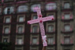 FILE - In this March 8, 2019 file photo, Consuelo Salas holds up a pink cross marked with the name of her daughter Vitoria Pamela Salas, who was killed in 2017 at age 23, as she calls for justice, in the Zocalo, Mexico City's main square, following a march. Hundreds plan to take to the streets of Mexico City again Sunday, Sept. 8, 2019, to demand justice for women who have been killed, kidnapped and sexually assaulted. (AP Photo/Rebecca Blackwell)