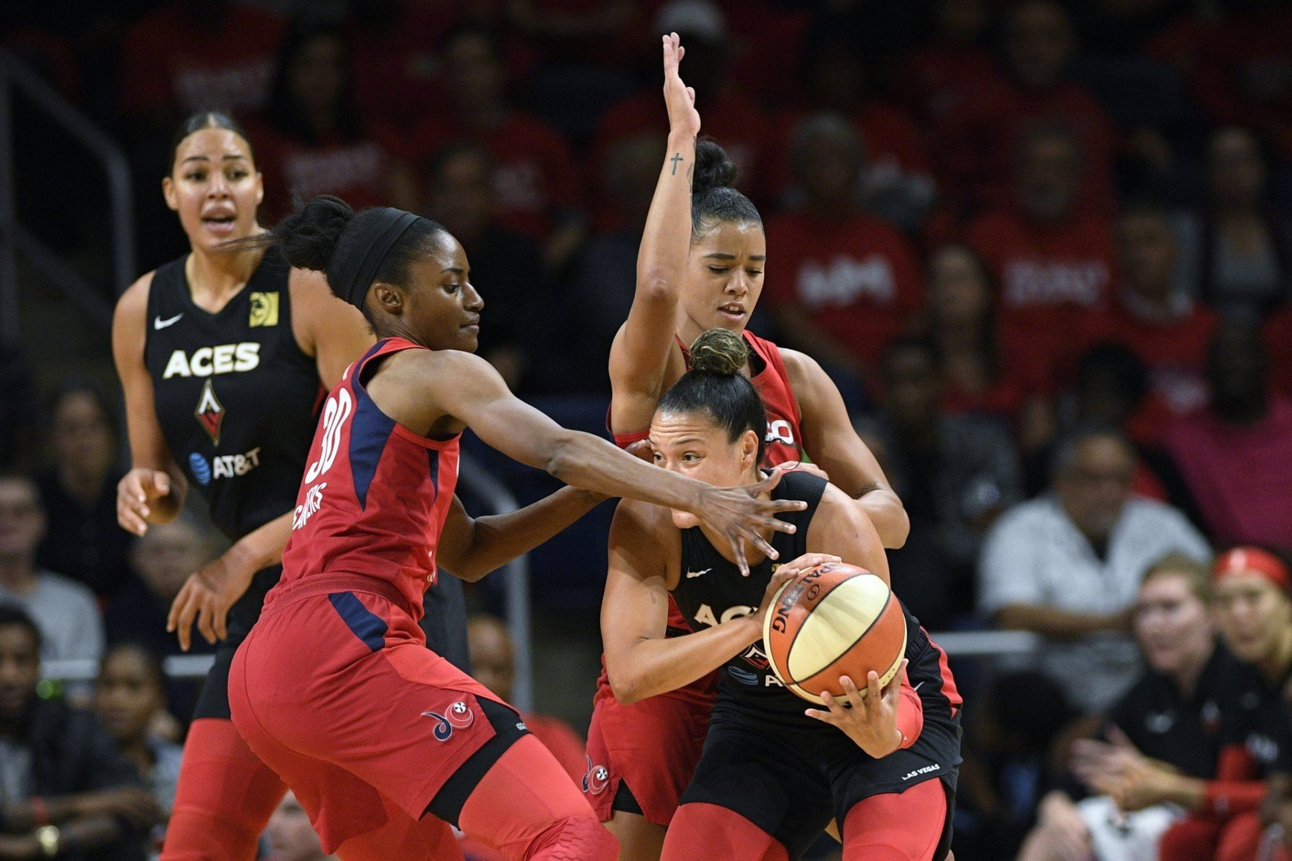 Las Vegas Aces guard Kayla McBride, right, tries to get past Washington Mystics forward LaToya Sanders, left, and guard Natasha Cloud, back right, during the first half of Game 2 of a WNBA playoff basketball series Thursday, Sept. 19, 2019, in Washington. (AP Photo/Nick Wass)