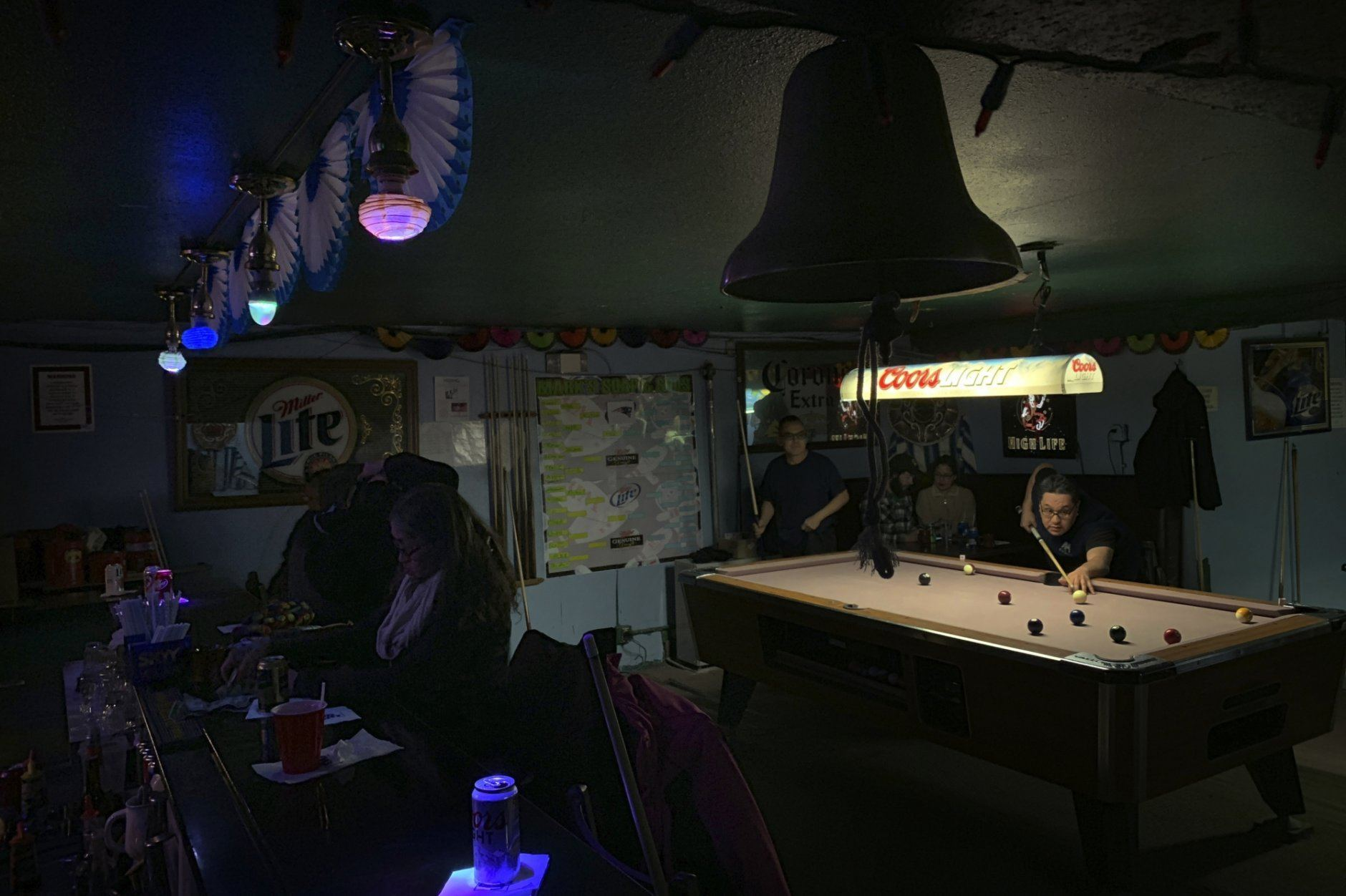 In this Feb. 23, 2019, photo, people play pool while some sit at the bar with their drinks at Soap and Suds, a popular nighttime spot, on Front Street in Nome, Alaska. (AP Photo/Wong Maye-E)