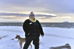 "In this Jan. 14, 2019 photo, Clarice ""Bun"" Hardy stands on the beach with her dog, Marley, in the Native Village of Shaktoolik, Alaska. Hardy, a former 911 dispatcher for the Nome Police Department, says she moved back to her village after a sexual assault left her feeling unsafe in Nome. (AP Photo/Victoria Mckenzie)"
