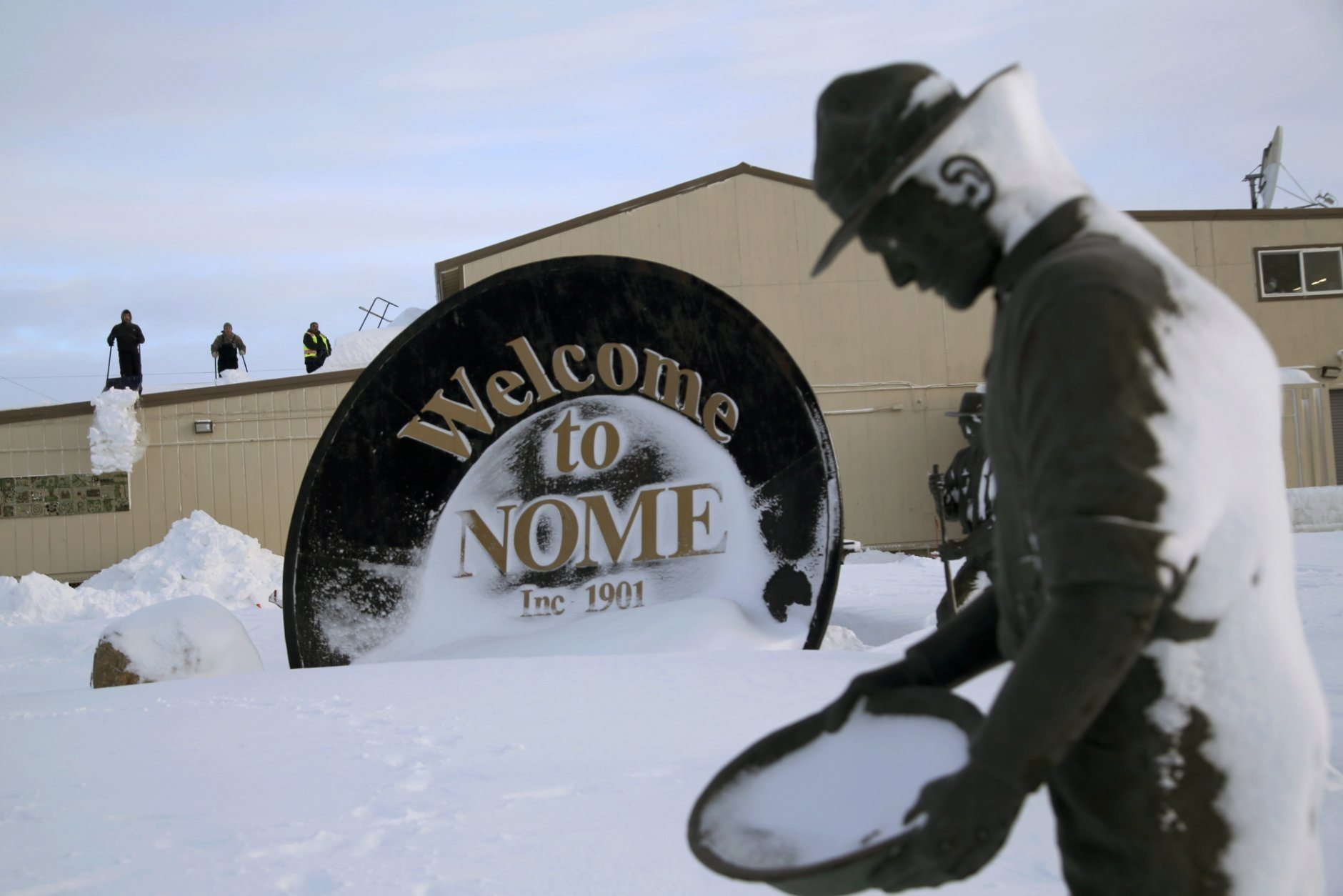 "In this Feb. 14, 2019, photo, three men shovel snow from the roof of a grocery store as a statue of one of the ""Three Lucky Swedes,"" credited with discovering gold in the late 19th century, stands in the foreground, in Nome, Alaska. The city later added statues of two native boys who led him to find the gold. (AP Photo/Wong Maye-E)"