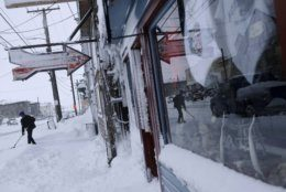 In this Feb. 22, 2019, photo, a man shovels snow outside the Polar Bar and Cafe on Front Street in Nome, Alaska. (AP Photo/Wong Maye-E)