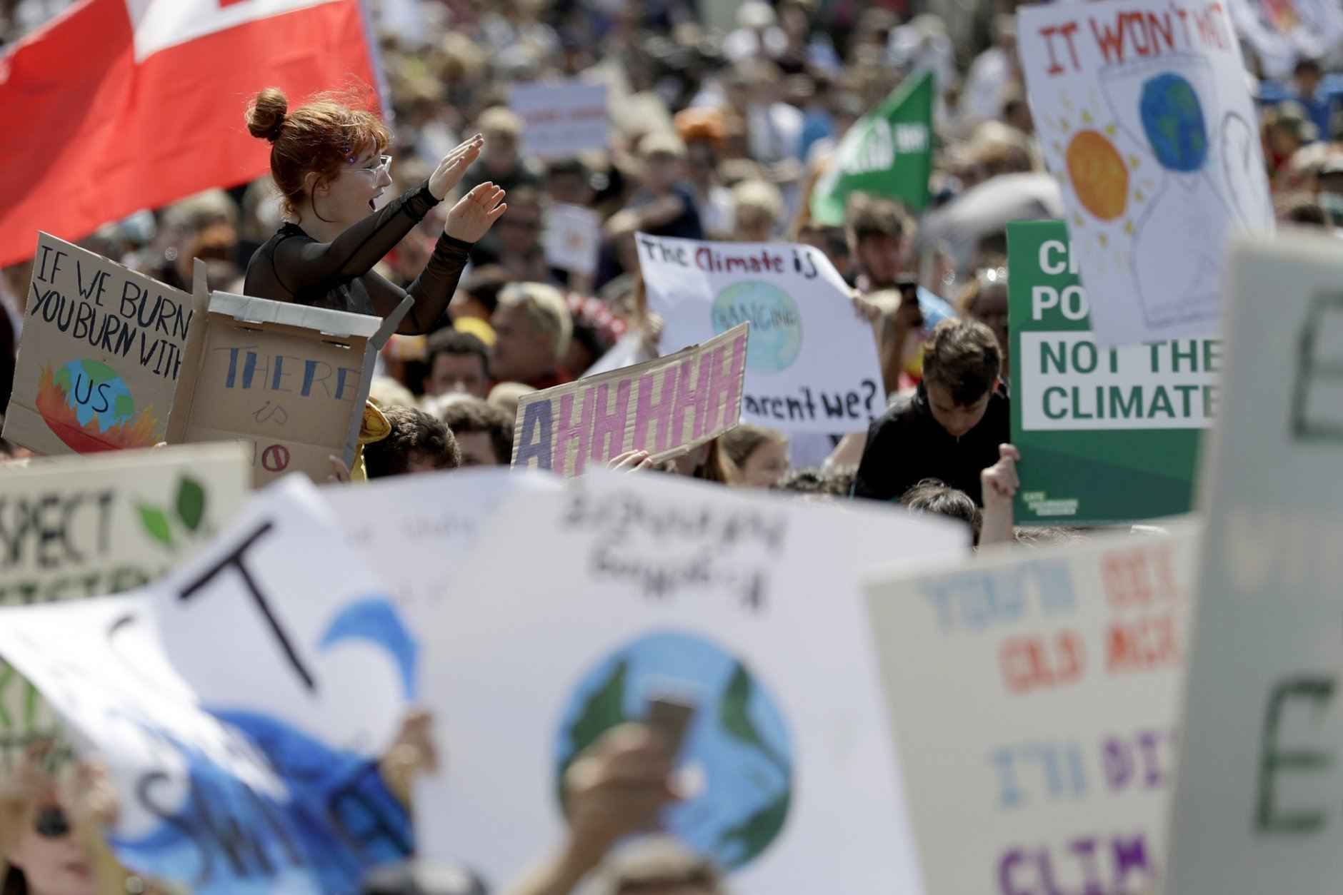 """A woman is lifted above the crowd as thousands of protestors, many of them school students, gather in Sydney, Friday, Sept. 20, 2019, calling for action to guard against climate change. Australia's acting Prime Minister Michael McCormack has described ongoing climate rallies as """"just a disruption"""" that should have been held on a weekend to avoid inconveniencing communities. (AP Photo/Rick Rycroft)"""
