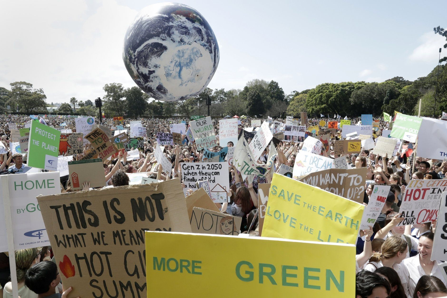 """A large inflatable globe is bounced through the crowd as thousands of protestors, many of them school students, gather in Sydney, Friday, Sept. 20, 2019, calling for action to guard against climate change. Australia's acting Prime Minister Michael McCormack has described ongoing climate rallies as """"just a disruption"""" that should have been held on a weekend to avoid inconveniencing communities. (AP Photo/Rick Rycroft)"""
