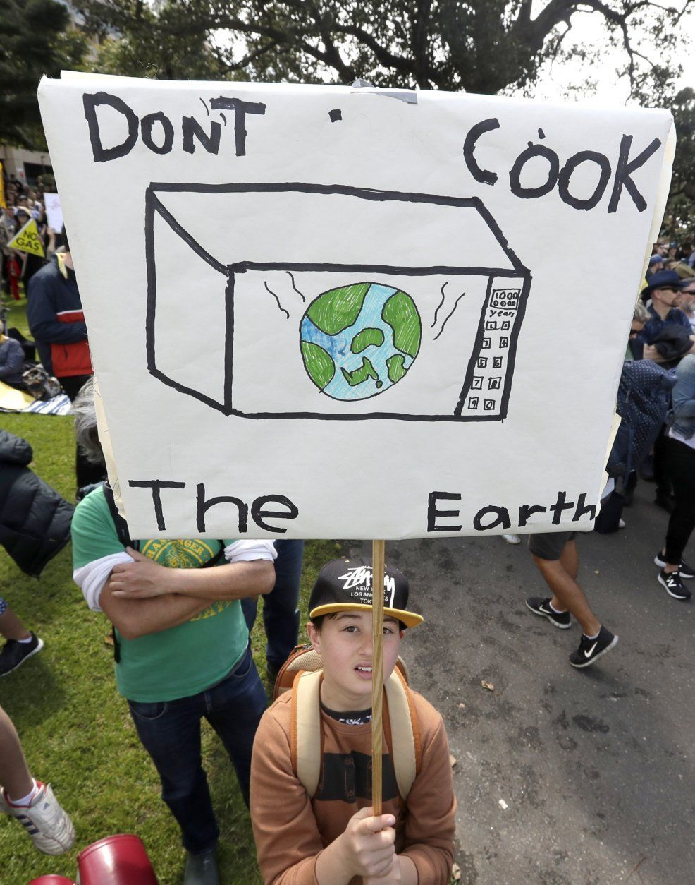 """A young activist holds up a handmade placard as thousands of protestors, many of them school students, gather in Sydney, Friday, Sept. 20, 2019, calling for action to guard against climate change. Australia's acting Prime Minister Michael McCormack has described ongoing climate rallies as """"just a disruption"""" that should have been held on a weekend to avoid inconveniencing communities. (AP Photo/Rick Rycroft)"""