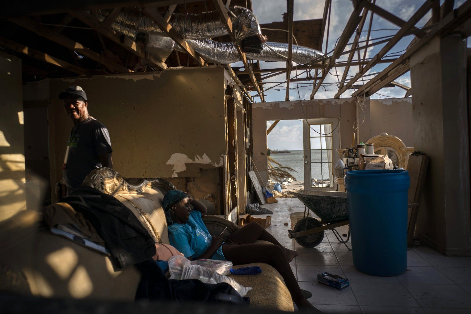 Phil Thomas, left, walks next to his daughter Ebony Thomas as she looks at her phone inside their home, shattered by Hurricane Dorian in Mclean's Town, Grand Bahama, Bahamas, Wednesday Sept. 11, 2019. Phil lost three members of his family in the Hurricane. (AP Photo / Ramon Espinosa)