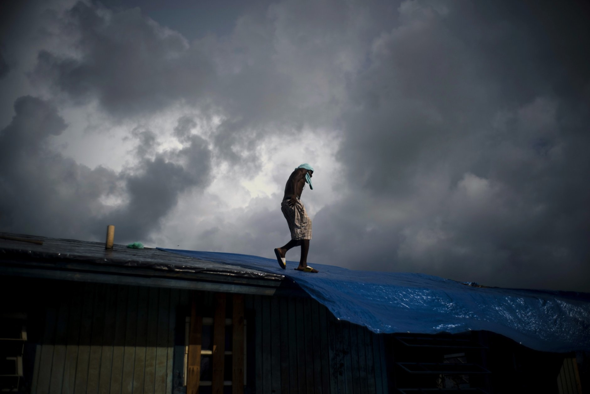 """Trevon Laing walks the roof of his house to repair the damage made by Hurricane Dorian, in Gold Rock Creek, Grand Bahama, Bahamas, Thursday Sept. 12, 2019. Trevor says """"After the hurricane they had me for dead, My momma was crying."""" When he returned, he said he found his brother crying on the front porch.""""I'm like, 'Hey, I'm not dead! You guys have no faith in me. I'm a survivor,'"""" he said, adding with a laugh, """"He was shocked and mad at the same time."""" (AP Photo / Ramon Espinosa)"""