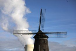 Steam rises from a nuclear power station behind an old windmill on the River Scheldt in Doel, Belgium, Thursday, Sept. 19, 2019. Political leaders meet Sept. 23, 2019 for a climate summit in New York to ramp up global efforts to tackle the climate crisis. (AP Photo/Virginia Mayo)
