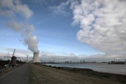 Steam rises from a nuclear power station next to an old windmill on the River Scheldt in Doel, Belgium, Thursday, Sept. 19, 2019. Political leaders meet Sept. 23, 2019 for a climate summit in New York to ramp up global efforts to tackle the climate crisis. (AP Photo/Virginia Mayo)