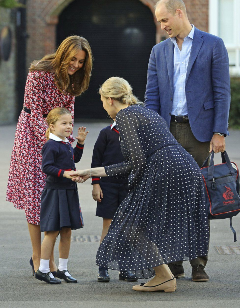 Helen Haslem, head of the lower school greets Britain's Princess Charlotte as she arrives for her first day of school at Thomas's Battersea in London, with her brother Prince George and their parents Prince William and Kate, Duchess of Cambridge, Thursday Sept. 5, 2019. (Aaron Chown/Pool via AP)