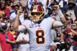 Washington Redskins quarterback Case Keenum celebrates touchdown run by teammate running back Adrian Peterson against the Dallas Cowboys in the first half of an NFL football game, Sunday, Sept. 15, 2019, in Landover, Md. (AP Photo/Mark Tenally)