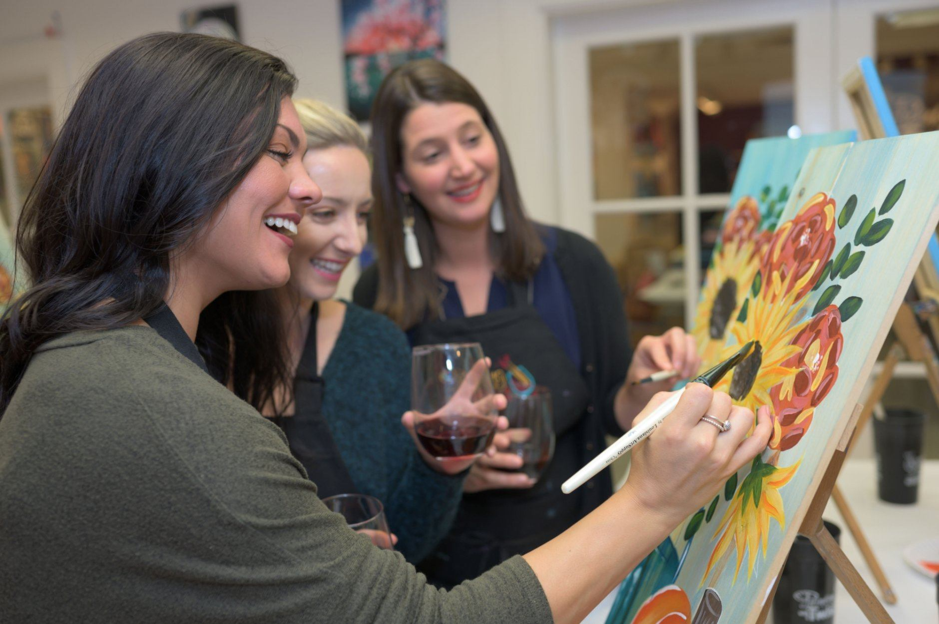 This 2019 photo provided by Painting with a Twist shows a group during a Painting with a Twist event in Mandeville, La. In recent years, the interactive painting industry has become a global sensation. Around the world, adults can spend their nights out learning to paint in a relaxed, BYOB setting. Thousands of franchises exist to help us all unleash our inner creative. (Painting with a Twist via AP)