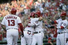 Washington Nationals' Gerardo Parra, second from left, celebrates his grand slam as he hugs Anthony Rendon, second from right, during the second inning of a baseball game against the Cleveland Indians, Saturday, Sept. 28, 2019, in Washington. Nationals' Asdrubal Cabrera (13) and Juan Soto, right, look on . (AP Photo/Nick Wass)