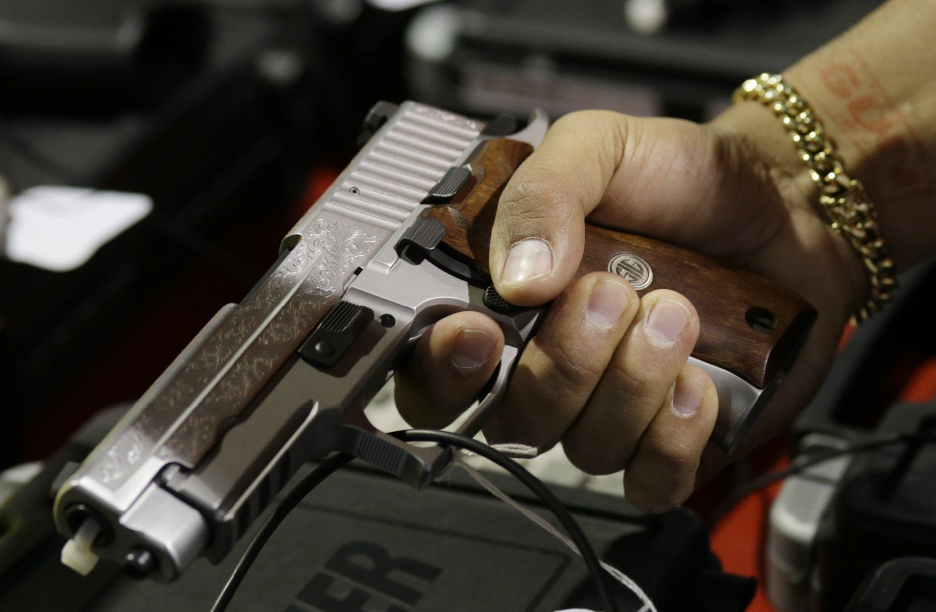 FILE - In this Jan. 9, 2016, file photo, a customer looks at a SIG Sauer hand gun at a gun show held by Florida Gun Shows in Miami.  The vast majority of mass shooters have acquired their firearms legally with nothing in their background that would have prohibited them from possessing a gun. But there have been examples of lapses in the background check system that allowed guns to end up in the wrong hands. Very few states also have a mechanism to seize firearms from someone who is not legally allowed to possess one. (AP Photo/Lynne Sladky, File)