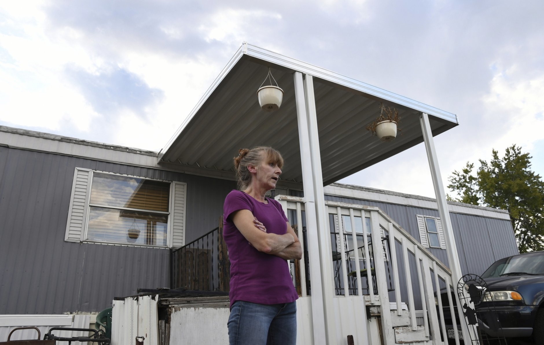 <p>In this Aug. 30th 2019 photo shows Karla Lyons, outside her mobile home at the Lamplighter Village in Federal Heights, Colo. Lyons&#8217; waitressing wages are eaten up by a constant stream of home and yard repairs ordered by her park manager, including removal of a giant maple tree that fell on her patio roof and crushed it. She would move if she could afford it. (Kathryn Scott/The Colorado Sun)</p>