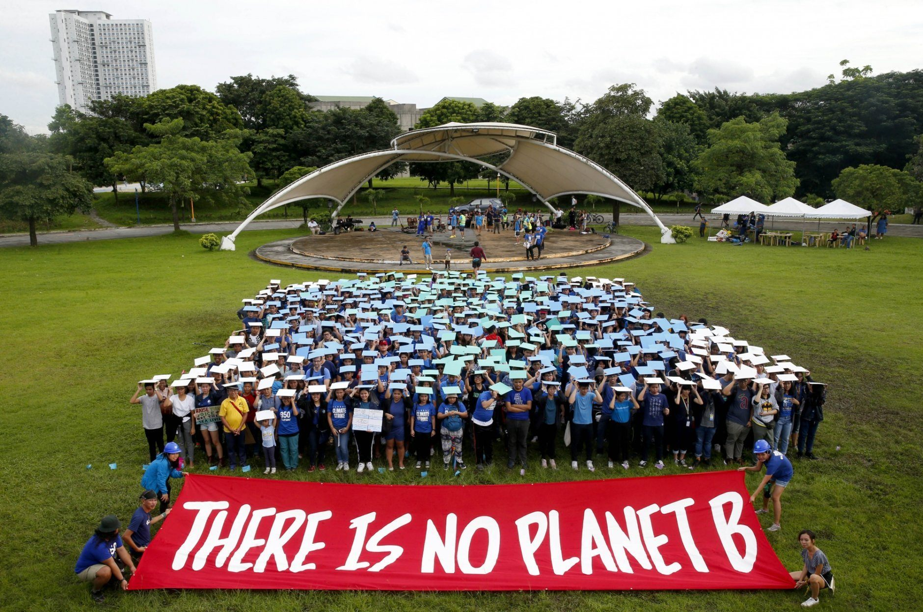 """Environmental activists, mostly students, display their message in front of """"a human globe"""" formation to coincide with the global protests on climate change Friday, Sept. 20, 2019, at the University of Philippines campus in suburban Quezon city northeast of Manila, Philippines. Various environmental groups in the country are participating in what is expected to be the world's largest mobilization on climate change known as """"Global Climate Strikes."""" (AP Photo/Bullit Marquez)"""