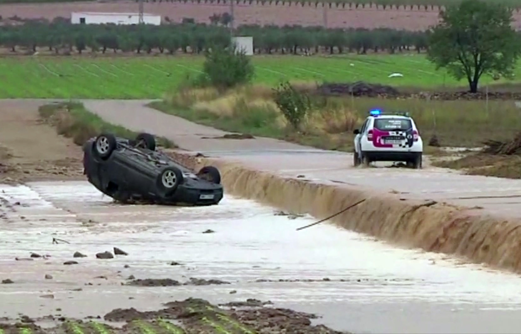 In this image made from video provided by Atlas, a police car drives to an overturned vehicle in which two people were drowned by floodwater, in Caudete, Spain, Thursday, Sept. 12 2019.  A large area of southeast Spain was battered Thursday by what was forecast to be its heaviest rainfall in more than a century, with the storms wreaking widespread destruction and killing at least two people. (Atlas via AP)