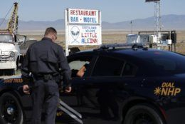 "Law enforcement officials stand outside of the Little A'Le'Inn, Wednesday, Sept. 18, 2019, in Rachel, Nev. Visitors descending on the remote Nevada desert for ""Storm Area 51"" are from Earth, not outer space. No one knows what to expect, but the two tiny towns of Rachel and Hiko near the once-secret military research site are preparing for an influx of people over the next few days. (AP Photo/John Locher)"