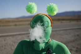 """Audrie Clark smokes a vape outside of the Storm Area 51 Basecamp event Friday, Sept. 20, 2019, in Hiko, Nev. The event was inspired by the """"Storm Area 51"""" internet hoax. Thousands of curious Earthlings from around the globe traveled to festivals, and several hundred made forays toward the secret Area 51 military base in the Nevada desert on Friday, drawn by an internet buzz and a social media craze sparked by a summertime Facebook post inviting people to """"Storm Area 51."""" (AP Photo/John Locher)"""