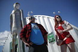 """Jackson Carter and Veronica Savage wait for passes to enter the Storm Area 51 Basecamp event Friday, Sept. 20, 2019, in Hiko, Nev. The event was inspired by the """"Storm Area 51"""" internet hoax. (AP Photo/John Locher)"""