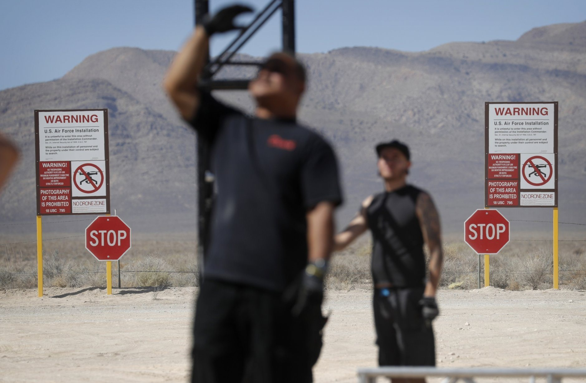 "Workers erect a stage near replica Area 51 gate signs at the Alien Research Center, Wednesday, Sept. 18, 2019, in Hiko, Nev. No one knows what to expect, but lots of people are preparing for ""Storm Area 51"" in the Nevada desert. Neighbors, elected officials and experts say the craze sparked by an internet joke inviting people to """"see them aliens"" might become a cultural marker, a dud or something in-between. (AP Photo/John Locher)"