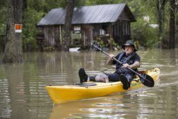 Donnie McCulley paddles out from a flooded neighborhood caused by heavy rain spawned by Tropical Depression Imelda with an armadillo as a passenger on Thursday, Sept. 19, 2019, in Patton Village, Texas. (Brett Coomer/Houston Chronicle via AP)