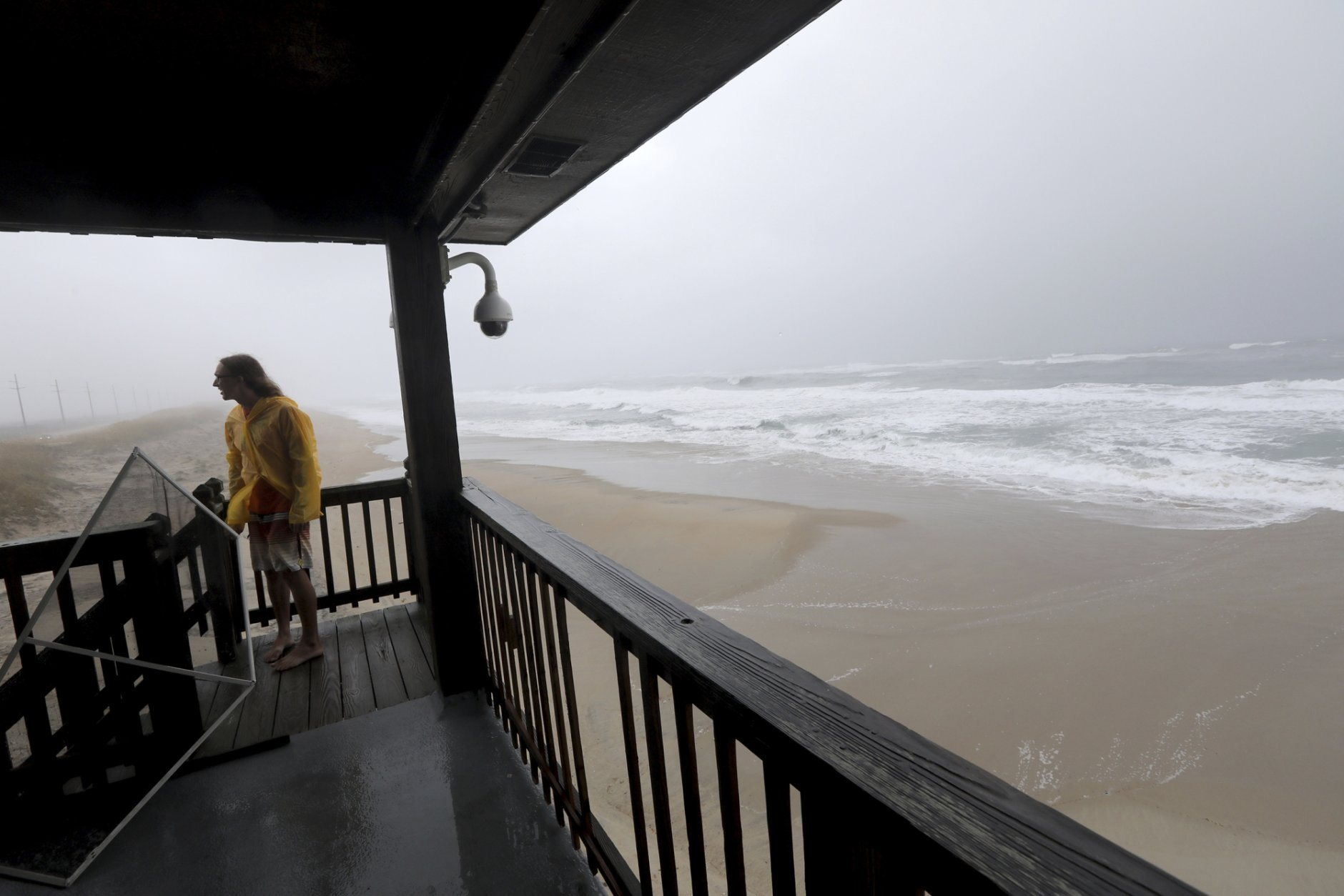 Hyatt Busbey gets a view of the ocean and sound as  Hurricane Dorian passes over Hatteras Island on Friday, Sept. 6, 2019 in Buxton, N.C. A weakened Hurricane Dorian flooded homes on North Carolina's Outer Banks on Friday with a ferocity that seemed to take storm-hardened residents by surprise. (Steve Earley/The Virginian-Pilot via AP)