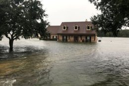 In this photo provided by the Chambers County Sheriff's Office, floodwaters surround a home, Thursday, Sept 19, 2019, in Winnie, Texas. The area has experienced heavy flooding due to Tropical Depression Imelda. (Brian Hawthorne/Chambers County Sheriff's Office via AP)