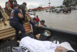 Dwain Kaufman, right, waits for his wife as she is helped into the back of a family member's truck by Beaumont firefighters and members of the Texas National Guard on Thursday, Sept. 19, 2019, in Beaumont, Texas. The remnants of Tropical Storm Imelda unleashed torrential rains in parts of Texas, prompting hundreds of water rescues, a hospital evacuation and road closures as the powerful storm system quickly drew comparisons to 2017's Hurricane Harvey. (Jon Shapley/Houston Chronicle via AP)
