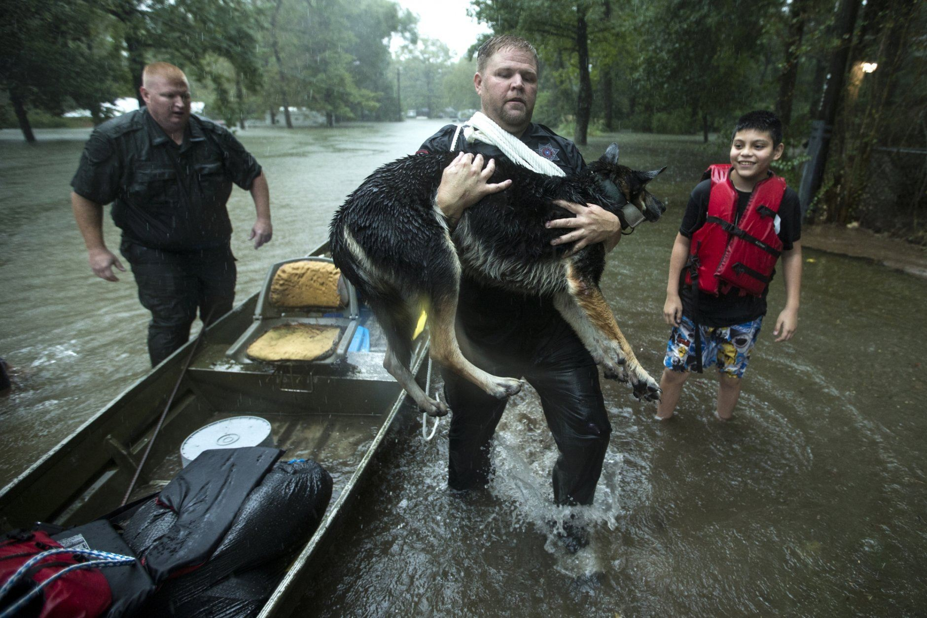 Splendora Police officer Mike Jones carries Ramiro Lopez Jr.'s dog, Panthea, from a boat after the officers rescued the family from their flooded neighborhood as rains from Tropical Depression Imelda inundated the area, Thursday, Sept. 19, 2019, in Splendora, Texas. (Brett Coomer/Houston Chronicle via AP)