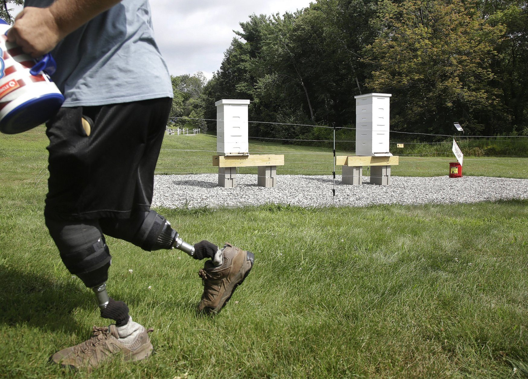 <p>In this Aug. 7, 2019 photo, U.S. Army veteran Oscar Toce cleans up after beekeeping at the Veterans Affairs&#8217; beehives in Manchester, N.H. Veterans Affairs has begun offering beekeeping at a few facilities including in New Hampshire and Michigan, and researchers are starting to study whether the practice has therapeutic benefits. (AP Photo/Elise Amendola)</p>