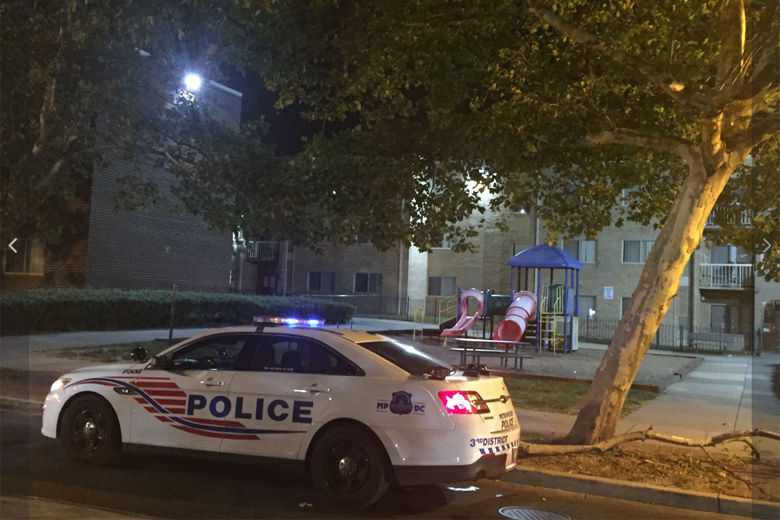 police car in front of complex in Columbia Heights where a shooting occurred