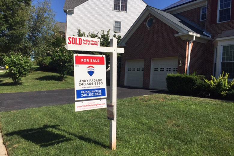 """For Sale"" sign in front of house"