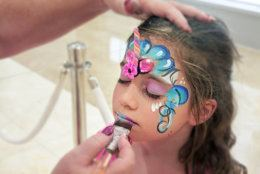 Young girl (age 8-9) getting her face painted by a face painting artist.