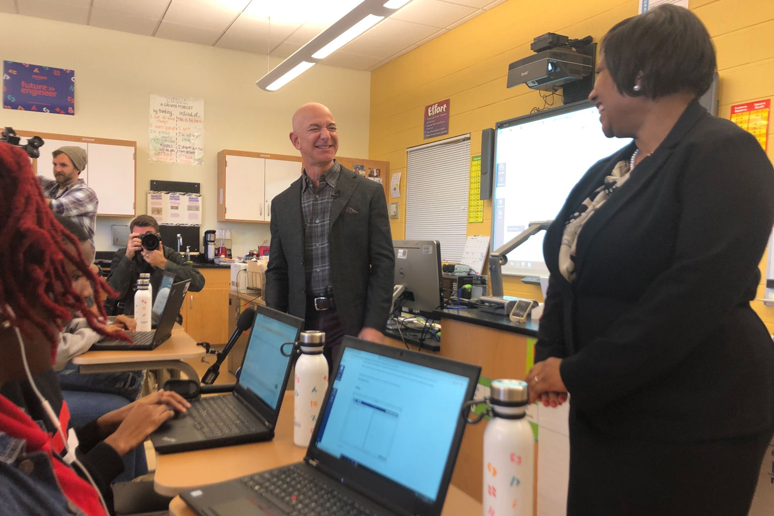 Amazon CEO Jeff Bezos shares a laugh with Dunbar computer science teacher Ramona Hutchins during his visit to her classroom. (WTOP/Melissa Howell)
