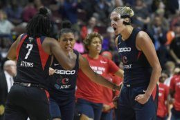 Washington Mystics' Elena Delle Donne, right, celebrates a play with Ariel Atkins, left, and Natasha Cloud, center, during the second half in Game 4 of basketball's WNBA Finals against the Connecticut Sun, Tuesday, Oct. 8, 2019, in Uncasville, Conn. (AP Photo/Jessica Hill)