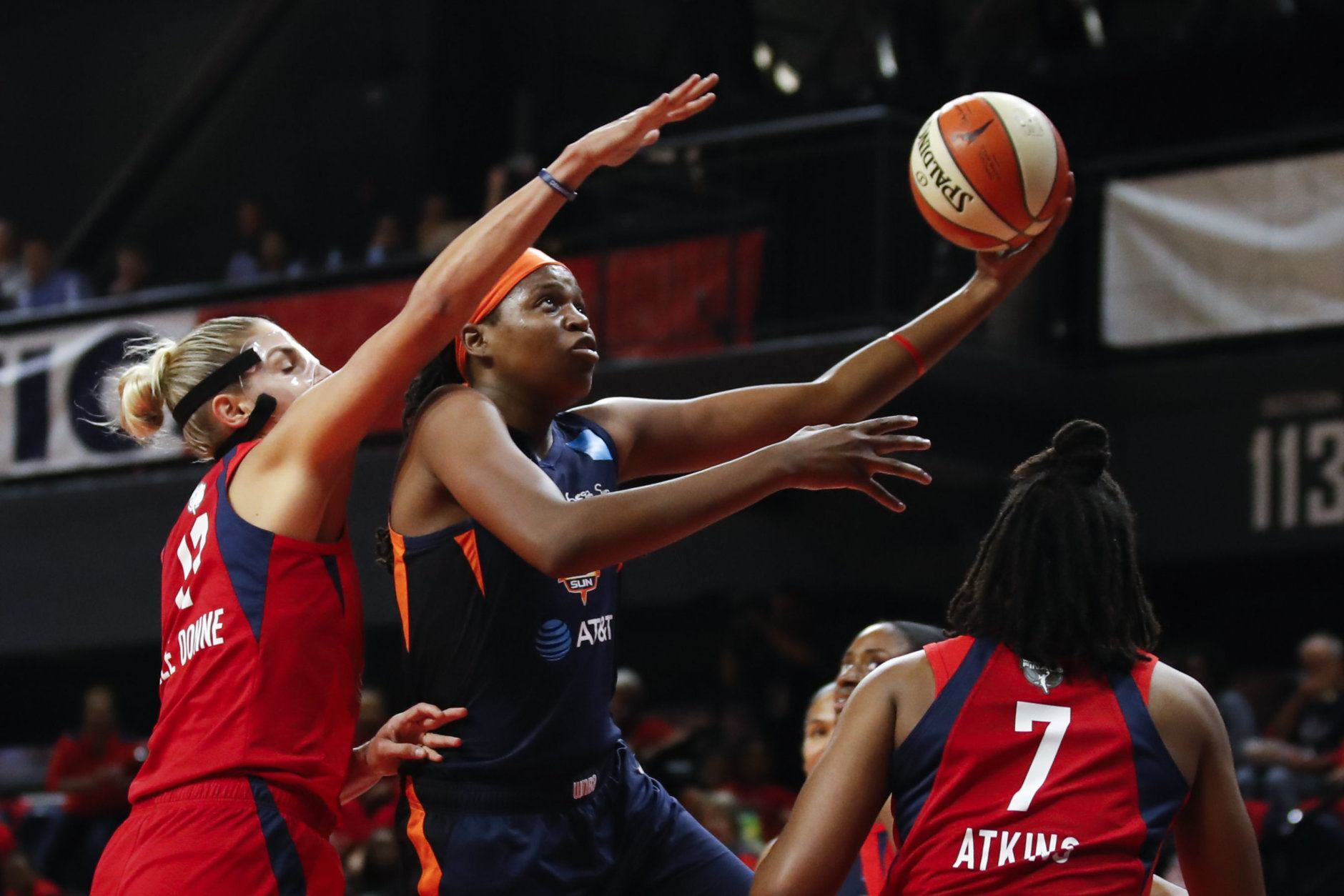 Connecticut Sun forward Jonquel Jones, center, shoots between Washington Mystics forward Elena Delle Donne, left, and guard Ariel Atkins during the first half of Game 5 of basketball's WNBA Finals, Thursday, Oct. 10, 2019, in Washington. (AP Photo/Alex Brandon)