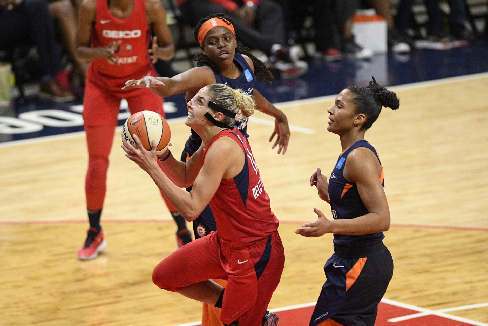 Washington Mystics forward Elena Delle Donne, front left, goes to the basket past Connecticut Sun forward Jonquel Jones, top, and forward Alyssa Thomas, right, in the first half of Game 5 of basketball's WNBA Finals, Thursday, Oct. 10, 2019, in Washington. (AP Photo/Nick Wass)