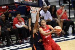 Washington Mystics forward Aerial Powers, right, goes to the basket against Connecticut Sun forward Morgan Tuck, left, in the first half of Game 5 of basketball's WNBA Finals, Thursday, Oct. 10, 2019, in Washington. (AP Photo/Nick Wass)