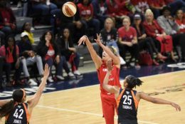 Washington Mystics forward Elena Delle Donne, center, shoots in front of Connecticut Sun center Brionna Jones (42) and forward Alyssa Thomas (25) in the first half of Game 5 of basketball's WNBA Finals, Thursday, Oct. 10, 2019, in Washington. (AP Photo/Nick Wass)