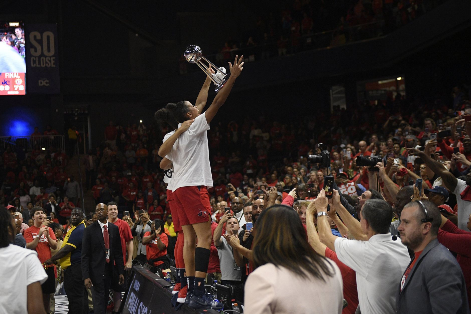 Washington Mystics guard Natasha Cloud raises the trophy to the crowd after Game 5 of basketball's WNBA Finals against the Connecticut Sun, Thursday, Oct. 10, 2019, in Washington. (AP Photo/Nick Wass)
