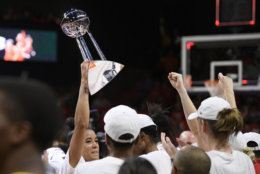 Washington Mystics guard Natasha Cloud holds up the trophy as they celebrate after Game 5 of basketball's WNBA Finals against the Connecticut Sun, Thursday, Oct. 10, 2019, in Washington. (AP Photo/Nick Wass)