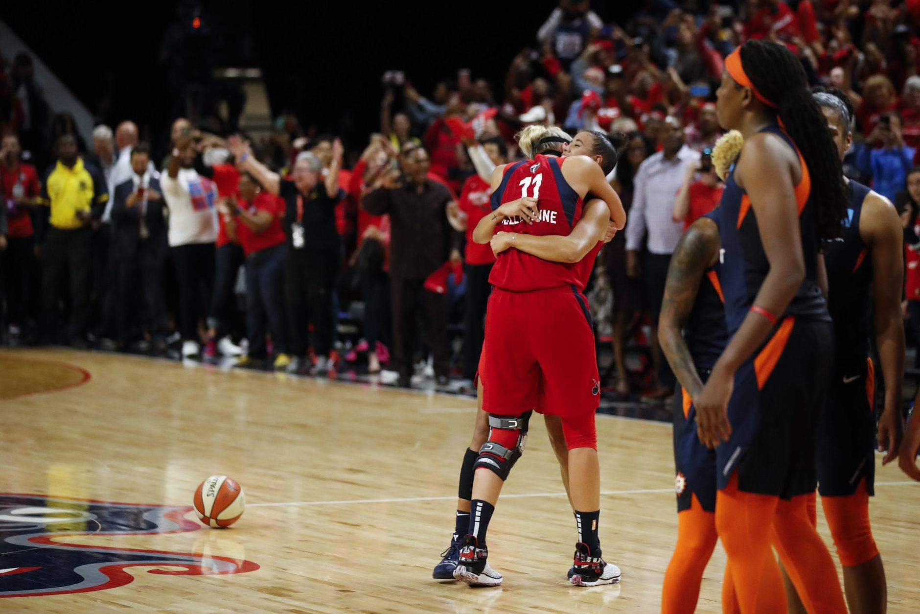Washington Mystics forward Elena Delle Donne (11) and guard Natasha Cloud hug as time expires in the second half of Game 5 of basketball's WNBA Finals against the Connecticut Sun, Thursday, Oct. 10, 2019, in Washington. (AP Photo/Alex Brandon)